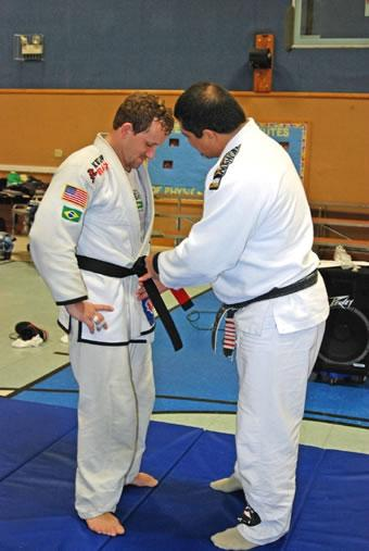 Professor Luiz Palhares tying the black belt around my waist for the first time.  December, 2006
